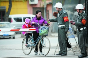 Resident shows ID card to get in the village. [Beijing News]