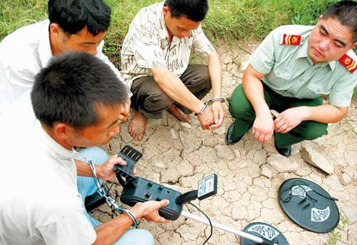 One of the three grave robbers who were caught by the police in southeast China's Zhejiang Province in 2007 is showing how to use a remote sensor.