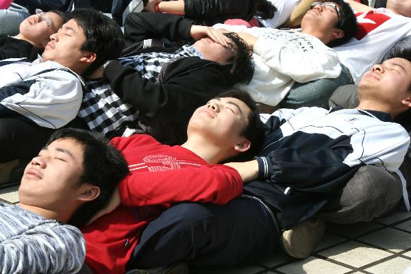 Senior-three students of Lintou Middle School take part in meditation training to ease anxiety in Hanshan County of Chaohu City, east China's Anhui Province, May 19, 2010. As the annually national college entrance examination draws near, Lintou Middle School held various activities to help students release pressure. [Xinhua]