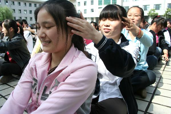 Senior-three students of Lintou Middle School give massage to each other to ease anxiety in Hanshan County of Chaohu City, east China's Anhui Province, May 19, 2010. As the annually national college entrance examination draws near, Lintou Middle School held various activities to help students release pressure. [Xinhua]