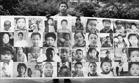 Guo Gangtang, a 40-year-old man from Shandong province who is looking for his missing son, holds a banner printed with photos of more than 400 missing children in a street in Wuhan, capital of Hubei province, on May 12.