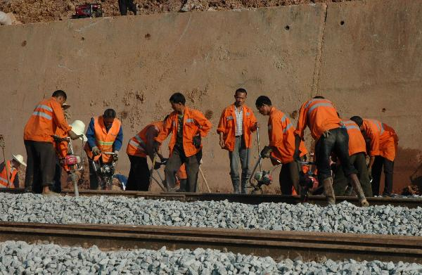 Railway workers reinforces the subgrade at a section of the Shanghai-Kunming railway line in Dongxiang County, east China's Jiangxi Province, May 24, 2010.