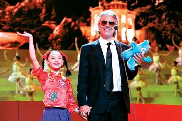 Italian singer Andrea Bocelli (R) hand in hand with a girl from Little Companion Art Troupe during the performance of opening ceremony for the Shanghai World Expo.