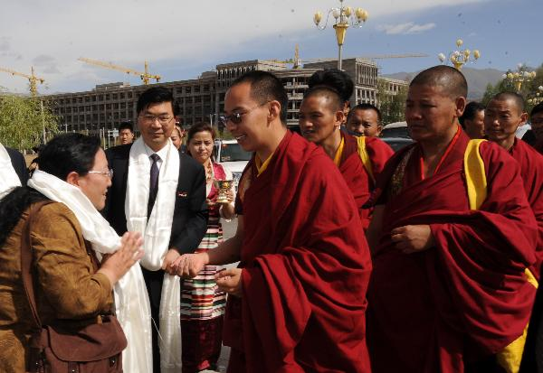 The 11th Panchen Lama (C) is welcomed by Professor Ceyang (L) of Tibet University in Lhasa, capital of southwest China's Tibet Autonomous Region, June 9, 2010. The 11th Panchen Lama visited Tibet University and Tibet College of Tibetan Medicine in Lhasa on Wednesday. (Xinhua