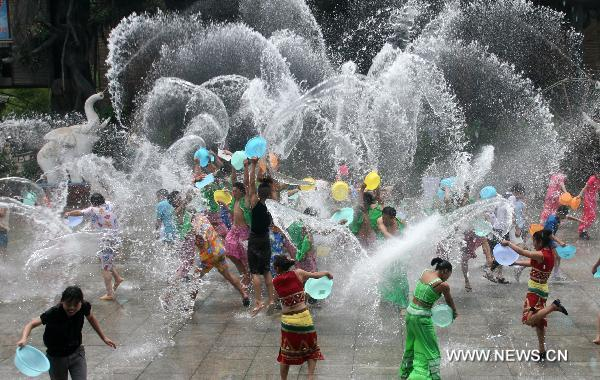 Girls and lads of Dai ethnic group go on furious fun of splashing water together with tourists, inside the Nine Pinnacle Tower Happy Land of Chinese Folk Custom, in Jinan, east China's Shandong Province, June 16, 2010. Series of funny activities including splashing water, contest of eating Zongzi, etc, are held inside the happy land to enable the tourists enjoying the saturnalia of coolness under the sultry summer season. [Xinhua/Lv Chuanquan]