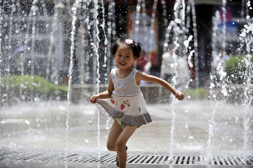 A girl runs through a fountain in downtown Lanzhou, capital of Gansu Province, on Friday, as the mercury rose to 40 C. [China Daily]
