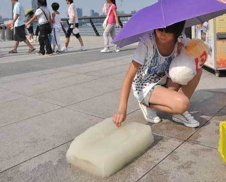 Blocks of ice were placed at the Bund Sunday to help visitors stay cool in the extreme heat when temperatures reached nearly 39 C. [Global Times]