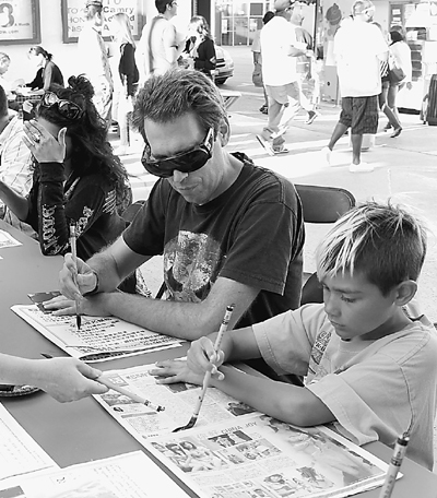 A father and his son learn to write Chinese calligraphy in the Confucius Institute, University of California in Los Angeles under the guidance of teachers, on August 7, 2010. Activities are held in Chinatown of Los Angeles every Saturday in August, including cultural performances, lectures on Chinese culture, and Chinese food cooking show.