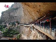 The Sky Bridge area, the next stop through the mountain, features a path built into the wall of the cliff and a temple below.  [Photo by Courtney]