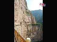 """A sign on the road through Mianshan points to the 'Cliff of Fear,' which is also known as """"Sacrifice Cliff."""" Like the Sky Bridge, the walkway of the Cliff of Fear is built right into the cliff of the mountain, and the path offers a great view of the valley below. [Photo by Courtney]"""