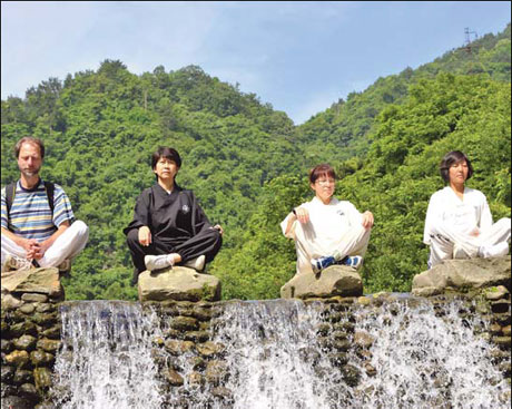 Four foreign Taoists sit for meditation in Xiaoyao Valley on Mount Wudang.