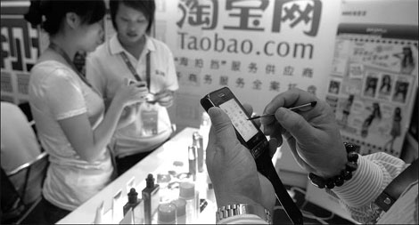 A taobao.com customer (right) shops online from his mobile phone. [China Daily]