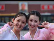 The DPRK performers from Pyongyang Art Troupe, dressed in traditional costumes, pose for a photo on the Tiananmen Square in Beijing during their touring trip to China, September 1, 2010. [Xinhua]