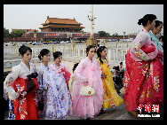 The DPRK performers from Pyongyang Art Troupe, dressed in traditional costumes on the Tiananmen Square in Beijing during their touring trip to China, September 1, 2010. [Chinanews.com]
