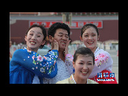 The DPRK performers from Pyongyang Art Troupe, dressed in traditional costumes, joke as they pose for a photo on the Tiananmen Square in Beijing during their touring trip to China, September 1, 2010. [Xinhua]