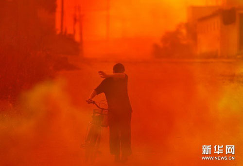 A worker walks along a street enveloped in yellow and red smoke in Jinhua city in east China's Zhejiang Province on Friday, September 17, 2010.