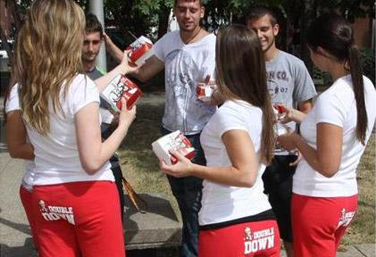 The American fast food chain KFC is currently promoting its new 'Double Down' sandwiches and has recruited attractive female college students to hand out coupons while wearing tracksuit bottoms with the 'Double Down' logo on their backsides.