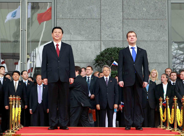 Chinese Vice President Xi Jinping (L) and Russian President Dmitry Medvedev (R) attend a flag-raising ceremony to mark Russia's National Pavilion Day at Expo Park in Shanghai, Sept 28, 2010. [Xinhua]