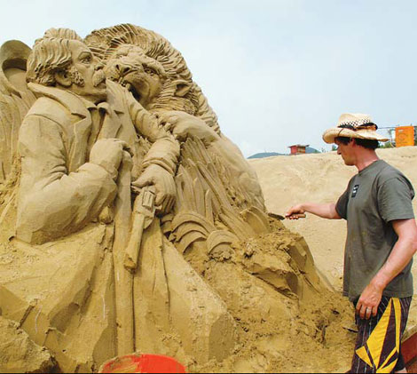 An artist puts the final touches to his sculpture. Provided to China Daily Island plays temporary home to exquisite beach art, Tang Zhihao reports.
