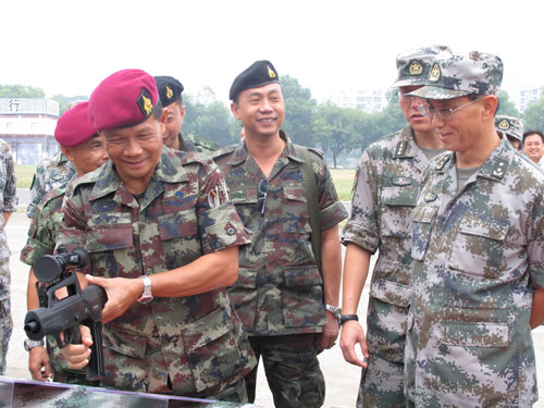 Royal Thai Army Special Forces Commander Lieutenant-General Podok Bunnag (L), accompanied by Deputy Commander of Guangzhou Military Command, Lieutenant General Zheng Qin (R), after the opening ceremony of 'Strike-2010' in Guilin, the Guangxi Zhuang autonomous Region, on Sept 8. [Cheng Guangjin/China Daily]