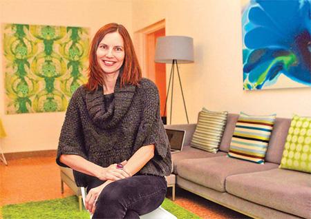 Swedish designer Eva Molina Biorck sits in the living room of her family home.
