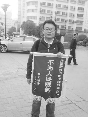 A young man holding a banner that reads 'Not for the People' can regularly be seen outside government offices in Wuxi City, Jiangsu Province. The message is directed at the local labor security authority.