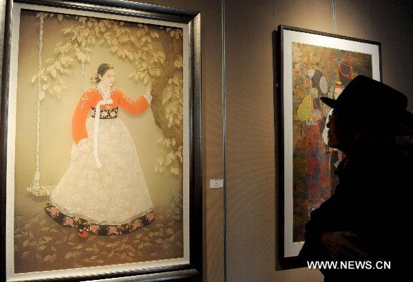 A visitor looks at a painting at an exhibition of heavy color ink painting in Beijing, capital of China, Nov. 25, 2010. The exhibition, cosponsored by China's art and painting institutions, displayed works of 87 Chinese painters.