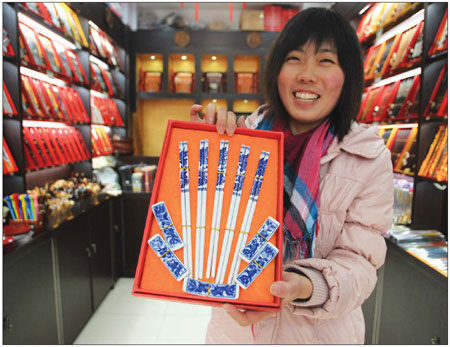 Creative designer Xing Junming shows off a decorative set of  chopsticks. Chinese zodiac animal designs are popular with  European tourists.