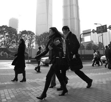 White-collar workers walk to work in Shanghai. Provided to China Daily