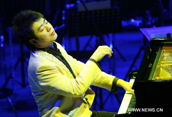 Renowned Chinese young pianist Lang Lang performs during his new year concert in Nantong, east China's Jiangsu Province, Dec. 10, 2010. [Ding Xiaochun/Xinhua]