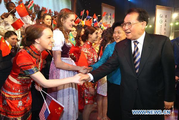Li Changchun(R), Standing Committee member of the Political Bureau of the Communist Party of China (CPC) Central Committee, shakes hands with the awarded student at the opening ceremony of the fifth conference of Confucius Institutes in Beijing, capital of China, on Dec. 10, 2010. [Yao Dawei/Xinhua]