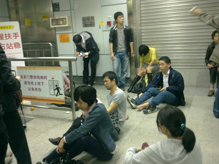 Dazed commuters sit on the ground of Guomao Station at Shenzhen's subway line No.1 Tuesday morning after a stampede triggered by a malfunctioning escalator left 25 people injured.