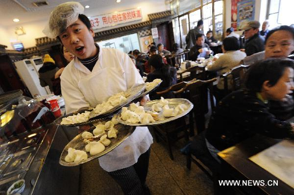 A waiter serves dumplings for customers at a restaurant in Beijing, Dec. 22, 2010, also the day of Dongzhi, the traditional Chinese winter solstice festival. People in north China have a tradition of eating dumplings on the festival to protect their ears from frostbite.