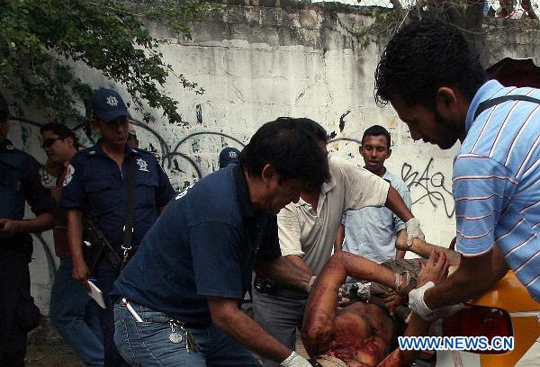 Forensic workers carry the body of a man in Acapulco, Mexico, on Jan. 8, 2011. Fifteen beheaded bodies were found Saturday morning in the Mexican beach resort of Acapulco, the public security office of Guerrero state reported. [Xinhua] 