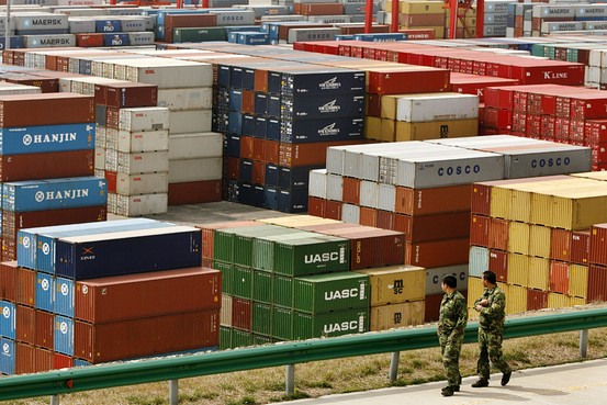 Workers walk amongst shipping containers at a port in China. The Ministry of Commerce said there is no immediate plan to launch more tax rebate policies, commenting on a report that several ministries are mulling cutting export rebates on certain products.