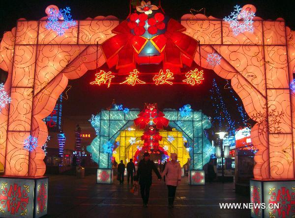 Pedestrians walk through an archway of lanterns on Shilu Street of Suzhou, east China's Jiangsu Province, Jan. 23, 2011. The city is in a festive mood as the Year of the Rabbit in Chinese lunar calendar approaches.