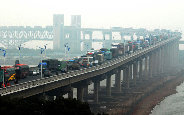 Cars wait in line on a section of Jiujiang Yangtze River Bridge, linking Jiujiang city of East China's Jiangxi province and Huangmei county of Central China's Hubei province, Jan 27, 2011. As many as 41,000 homecoming vehicles backed up on the bridge on Jan 26 and the gridlock lasted for nearly 20 hours. [Photo/Xinhua]