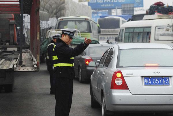 Traffic policemen direct the traffic on Jiujiang Yangtze River Bridge, in Jiujiang, Jan 27, 2011. [Photo/Xinhua]