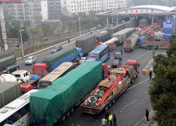 Cars wait in line to pass a toll station of the Jiujiang Yangtze River Bridge in Jiujiang, Jan 27, 2011. [Photo/Xinhua]