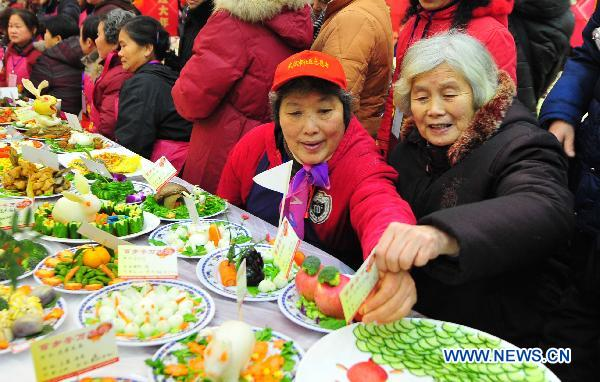 The 78-year-old resident Cao Manrong (1st R) tastes dishes during a grand feast held at the Baibuting Community in Wuhan, capital of central China's Hubei Province, Jan. 27, 2011.