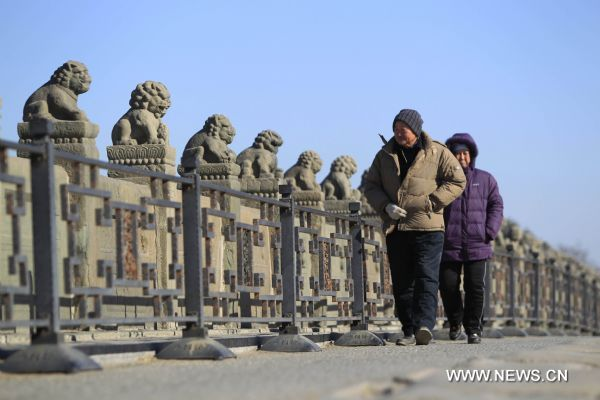 Two pedestrians walk on the Lugou Bridge, or Marco Polo Bridge in Beijing, capital of China, Jan. 29, 2011. Beijing breaked a 60-year record for the latest date for its first snowfall of the season on Saturday. Since 1951, the latest record of the first snowfall in Beijing was in 1984, when it arrived on Jan. 29.