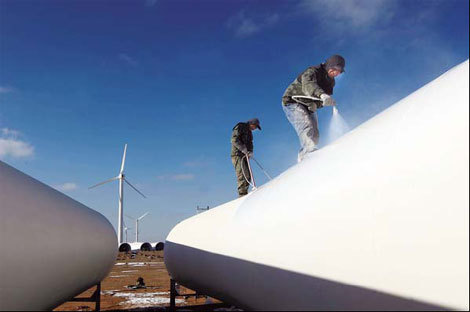 Workers paint wind turbines in Yumen, Gansu province. Due to poor transmission capabilities and grid connection in Northwest China, new wind projects are being built in other provinces. [China Daily via agencies]