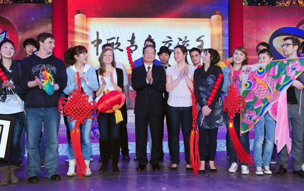 Chinese Premier Wen Jiabao stands with young people from both China and Europe at the opening ceremony of the China-EU Year of Youth in Beijing Feb 23, 2011. [Photo/Xinhua]