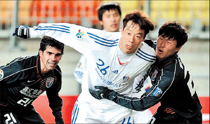 Shanghai Shenhua's Wu Xi (right) tries to hold back Suwon Bluewings' Yeom Ki-hun (center) during their AFC Champions League match in Suwon yesterday.  