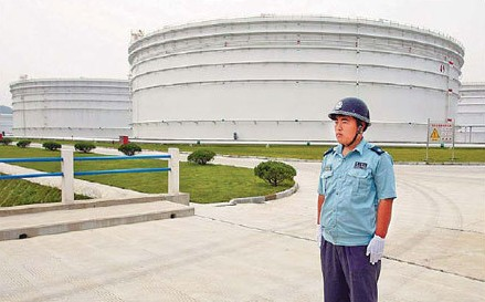 An armed police officer stands guard near large oil tanks at Zhenghai National Oil Reserve Base in Ningbo, Zhejiang province. China started to build oil reserve bases as early as 2003 to offset supply risks and reduce the impact of fluctuating energy prices.