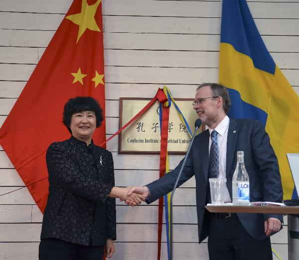 Gu Liya (L), the Communist Party Secretary of the Southwest Jiaotong University, shakes hands with Thomas Blom, Principal of the Karlstad University during the inaugural ceremony of the Confucius Institute in Karlstad, Sweden, March 29, 2011.