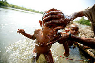 Bathing a young child in the April River, Pukapuki village, Papua New Guinea. [WWF]
