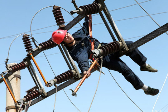 A technician checks a high-tension wire on April 11 to ensure that mineshafts at a coal mine company in Huaibei, Anhui province, are receiving power in a safe way. [Huang Shipeng/China Daily]