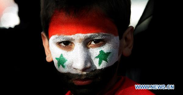 A Syrian boy with Syrian national flag painted on his face is seen during a sit-in attended by scores of Syrians living in Jordan against Bashar's government and the ruling Baath Party in front of Syrian embassy in Amman, capital of Jordan, on April 17, 2011. [Mohammad Abu Ghosh/Xinhua]
