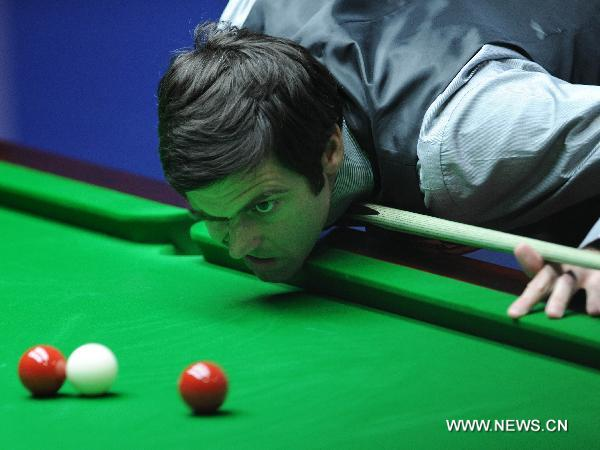 Ronnie O'Sullivan of England takes a close watch of the balls during his first round match against Dominic Dale of Wales in 2011's World Snooker Championship in Sheffield, Britain, April 18, 2011. O'Sullivan leads by 7:2. (Xinhua/Zeng Yi)